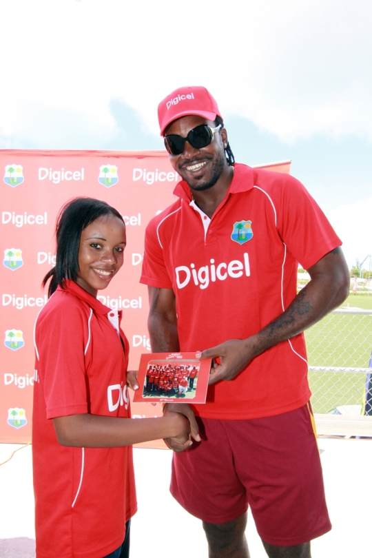 Chris Gayle presents one of two female participants with an autographed photo